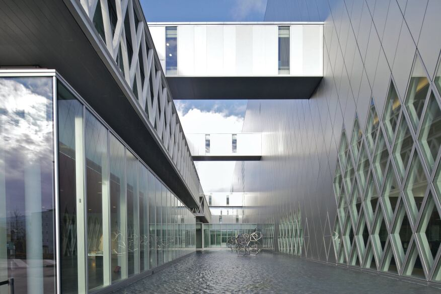 Between the two structures is a courtyard spanned by bridges that link the volumes at different levels.
