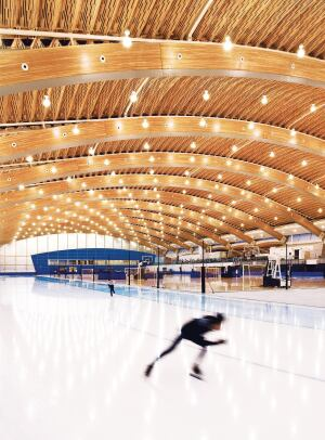 The roof of the Richmond Oval is made up of large Douglas fir glulam arches, with ribbed panels made from recovered wood devastated by a pine beetle infestation in the interstitial spaces.