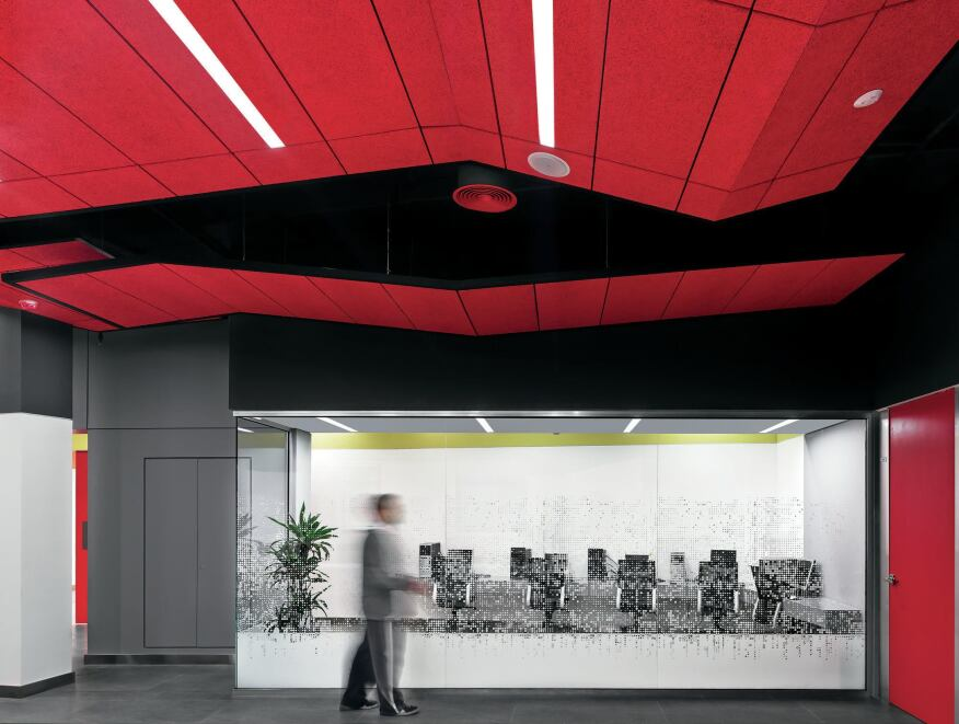 In certain areas of the building with high ceilings, such as the study rooms, a suspended ceiling of floating tiles made from acoustical material helps to give the space a more intimate sense of scale while also incorporating linear lighting components and sprinklers.