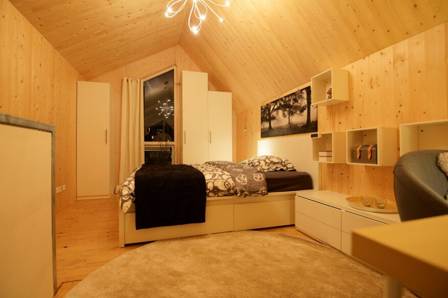 The loft-style bedroom stands alone on the second floor of the home and features built-in storage space.