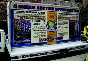 STREET MARKETING: Aggressive marketing, such as this rolling billboard, is common  before a real estate auction.
