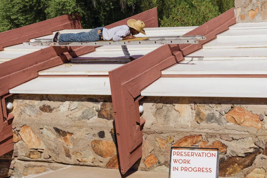 A maintenance worker removes deteriorated sealant from the acrylic panels that top the controversial canvas roofs over the historc core of Taliesin West, to 10-acre compound designed by Frank Lloyd Wright.