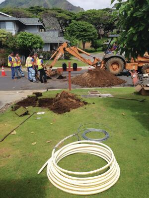 Trenchless rehabilitation with new CPVC composite service line being pulled in at the water meter in Maui, Hawaii.