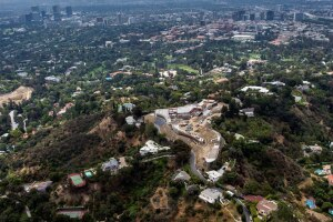 Buildings in downtown Los Angeles stand in the distance as construction continues at a home being built by Nile Niami, a film producer and speculative residential developer, in this aerial photograph taken in Bel Air, California, U.S., on Monday, May 18, 2015. Niami, who hopes to sell the house for a record $500 million, is pouring concrete in L.A.ís Bel Air neighborhood for a compound with a 74,000-square-foot (6,900-square-meter) main residence and three smaller homes, according to city records. Photographer: David Paul Morris/Bloomberg