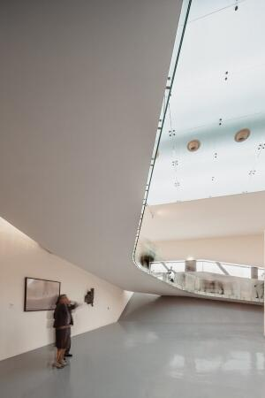 The cantilevered concrete ramp by Mateo Arquitectura helps erase the spatial distinction between floors, allowing visitors to focus on the center's artwork.