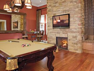 GAME TIME: A flat-panel plasma television and a propane fireplace set into an aggregate flagstone surround (above) provide just one area of entertainment in the game room. A window seat with in-bench storage can be a quiet retreat, while ample access to the loggia and its outdoor kitchen—not to mention a home theater nearby—offers additional options.