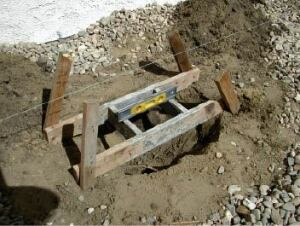 Figure 1. The form for the top of the footing is made from 1x4s fastened together at a slight angle. Four stakes support it and keep it level above the footing hole.