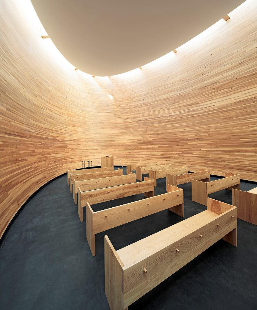 Indirect light spills down the double-curved walls, which are fashioned from oiled alder planks glued together to form one large wooden bowl. The 4¾-inch-by-1¾-inch alder planks were CNC–milled into 7,500 distinct shapes. The structure floats on a concrete foundation, allowing for thermal movement.