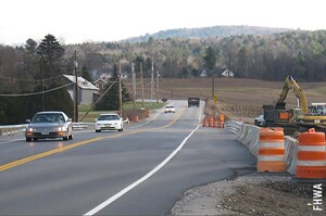 Traffic is shown moving on the completed FHWA, Highways for LIFE project with Vermont Department of Transportation (Vtrans) that used ABC and innovative technology to provide a single span, highly durable, integral abutment bridge. The superstructure used weathering steel girders, had a bare high performance concrete (HPC) deck reinforced with solid stainless steel, and was topped with a curbless deck rail.