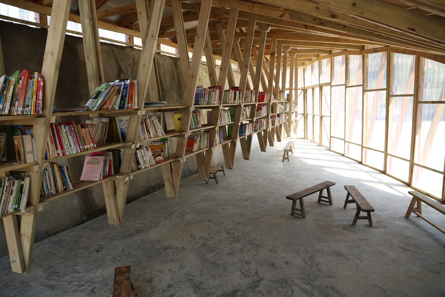 The roof trusses support 12 bays of wood bookshelves, each holding 200 books.