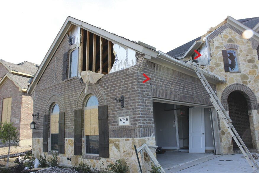 In one case, brick veneer and foil-faced foam sheathing were both blown off the gable wall—possibly after the wind breached the garage door.