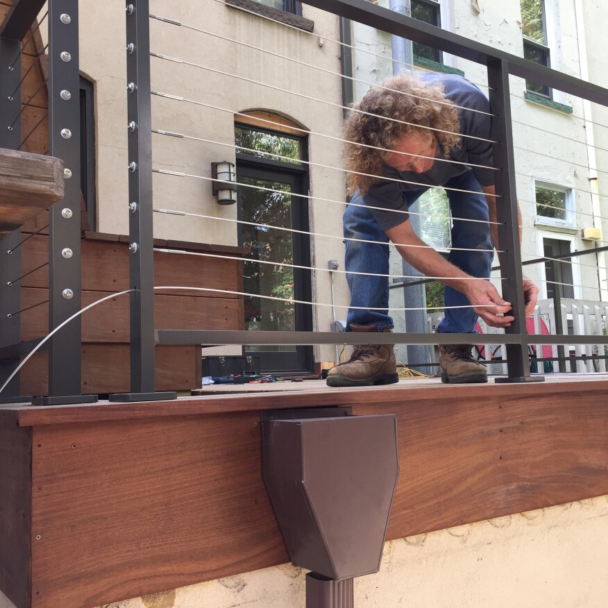 Water drains from the deck through a large scupper in the curb and runs through a custom-fabricated leader head. The powder-coated aluminum deck railing is also custom-fabricated.