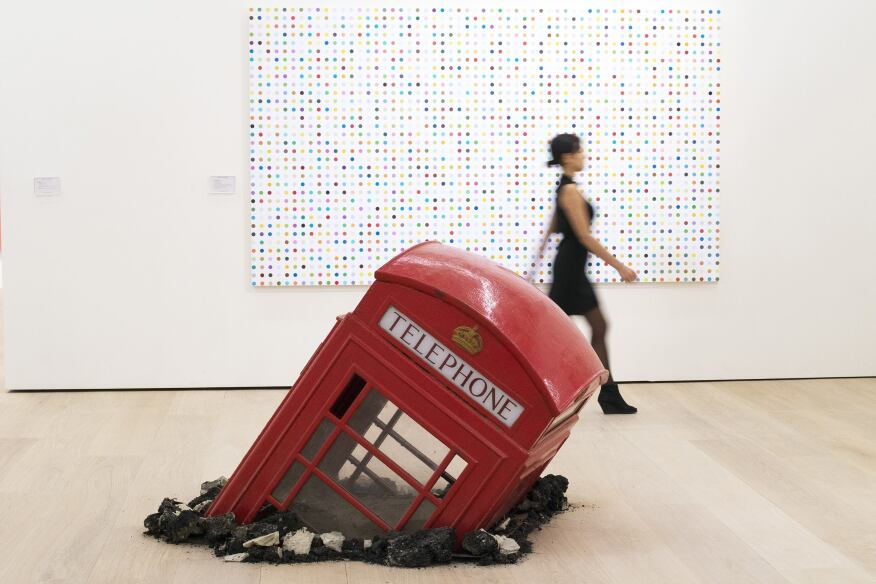 """Artist Damien Hirst's """"5-Fluorotryptamine"""" and Banksy's """"Submerged Phone Booth"""" are on display at Phillips' new headquarters and exhibition space in London designed by architecture firm Aukett Fitzroy Robinson. The art auctioneer celebrated the opening of the new space with an inaugural public exhibition of contemporary sculpture curated by Francesco Bonami."""