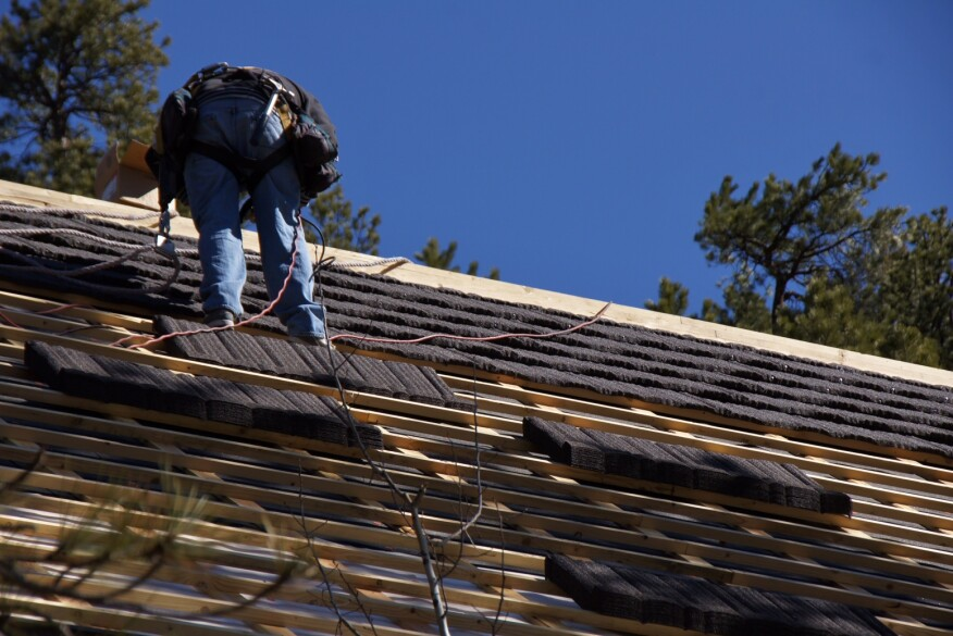 A worker for Horn Brothers Roofing installs stone-coated metal roofing on a large, Colorado home. The steep roof measures 9,400 square feet.