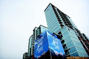"FIRST GLANCE: An imposing billboard, with the tagline ""Own the Sky,"" was the only visible advetising the developers of Glass House used to promote their building.  That signage directed people to the project's Web site, where they could register to receive more information."