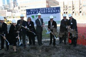 Village Green chairman and CEO Jonathan Holtzman (third from right) joins a development team including representatives from US Bank, the Minneapolis City Council, and Minneapolis mayor R.T. Ryback (fourth from right) for the groundbreaking of the $33 million Mill District City apartments.