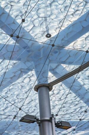 The lower membrane pattern is mostly transparent, while the upper pattern is more opaque to block light pollution at night. An irregular network of steel cables work with the canopy's steel frame to help support the membrane.