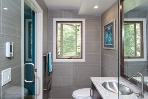Barsoum removed the existing heat register under the window and replaced it with electric heat under the diagonally laid porcelain tile floor. A wall-mounted towel warmer in front of the toilet provides additional heat.
