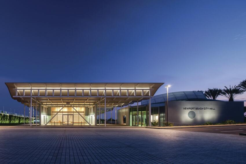 "The north end of the complex also provides the public entry for visitors arriving by car, which, in Newport Beach, is most of them. The council chamber volume (at right) is enclosed by a curving roof that offers both sunshading and wayfinding. ""This civic center happens in a really suburban context,"" says Steven Chaitow, AIA, principal and project manager for Bohlin Cywinski Jackson. ""We needed something that announces the civic center to people driving by at 60 miles per hour."""