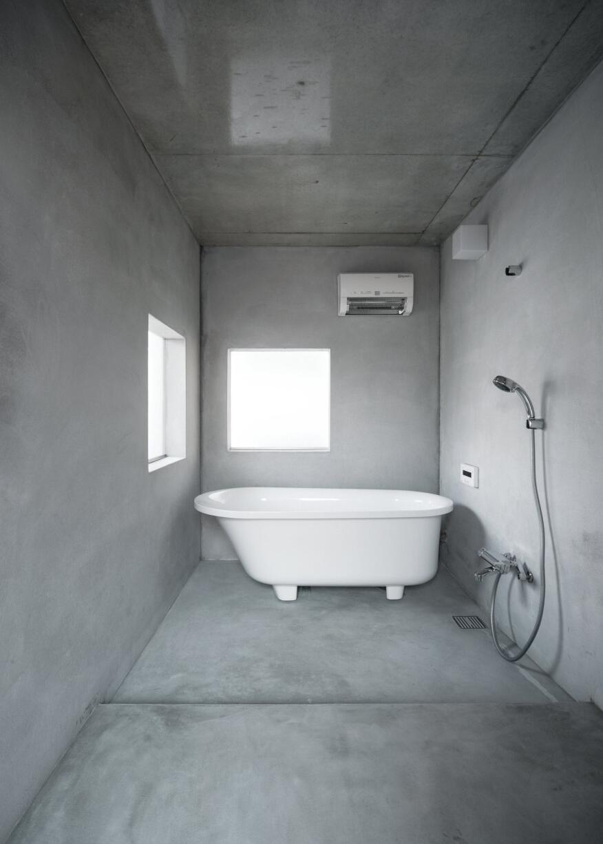 The concrete-lined bathroom is situated just behind the kitchen on the second floor—polycarbonate windows harvest diffuse light from the house's interior to bring into the minimal space.