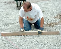 Concrete slabs perform best when they are even thickness. The worker shown here is using a 2x4 to strike flat subgrade. Drylines serve as a guide to ensure that the subgrade has proper elevation.