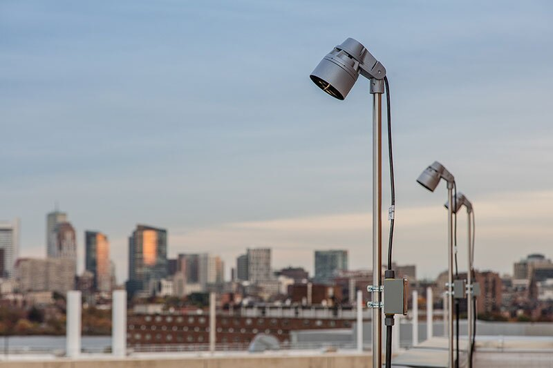 The fixtures that illuminate the site are pole-mounted on the surrounding buildings.