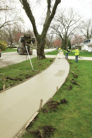 Suburban Concrete of Mundelein, Ill., finishes replacing sidewalks in one of 30 communities participating in a shared-purchasing program. Other joint bids include water meter testing, sewer lining, and hydrant painting.