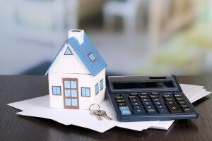 Toy house and calculator on table close-up; Shutterstock ID 200470286