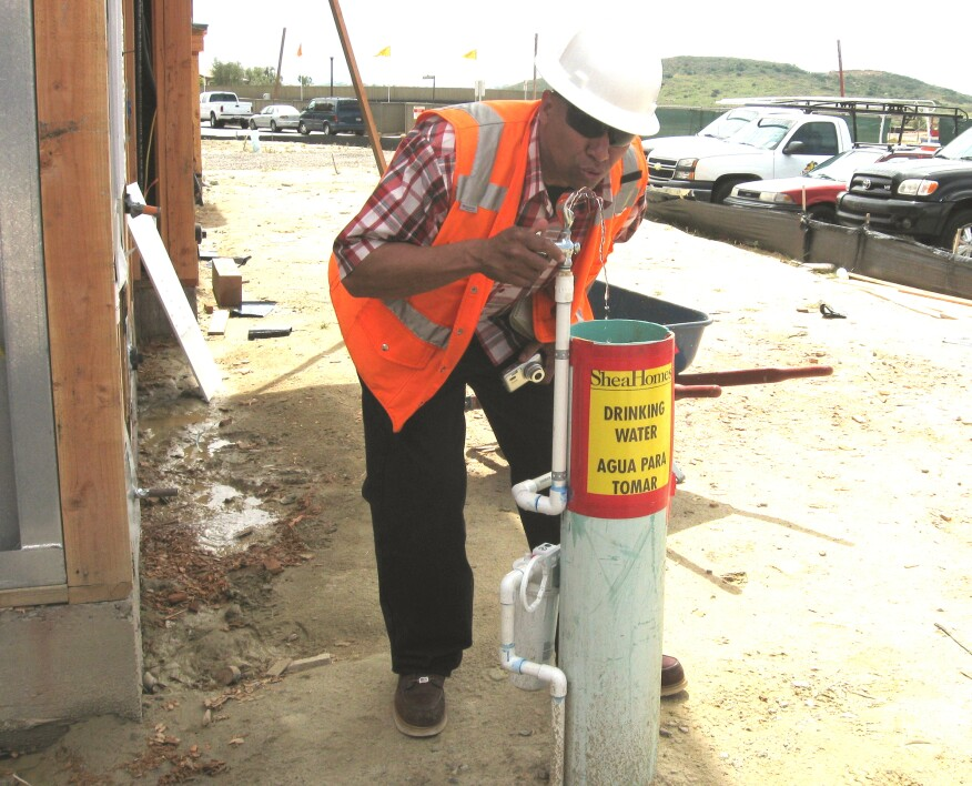 Every contractor or subcontractor with employees on a site is required to supply water for its own employees. That's not the developer's responsibility. But developers or general contractors are free to supplement the employer-supplied water if they choose to do so. Here, the author takes a drink from a water fountain set up by Shea Homes, the developer and prime contractor on this site. Shea routinely makes water fountains available to all the workers on sites they control.