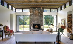 Chiaroscuro Effect. A tier of clerestory windows wraps around the dining and living rooms, providing a sense of separation between walls and roof plane. The window frames, which match the dark-stained exterior siding, highlight the contrast between structure and openings.