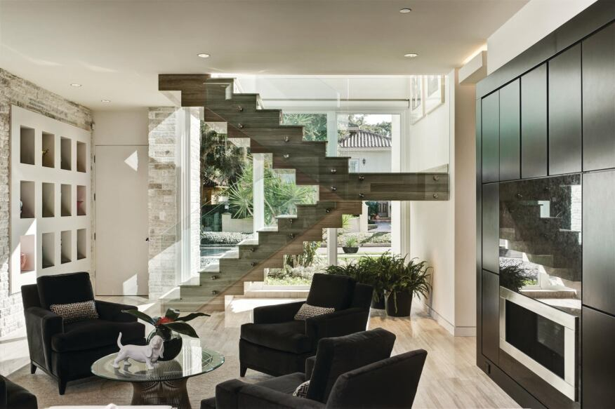 Staircase The home's open-riser stone staircase is a signature element, appreciated from inside and out. A transparent glass balustrade makes it appear to float in space, while the stair's location at the edge of the family room keeps it from intruding on the open floor plan and traffic patterns. It's also an iconic and ironic counterpart to an adjacent elevator, a contemporary must-have for aging owners. A series of niches at the base of the stairs, which are reminiscent of the front-door design, display colorful art elements.