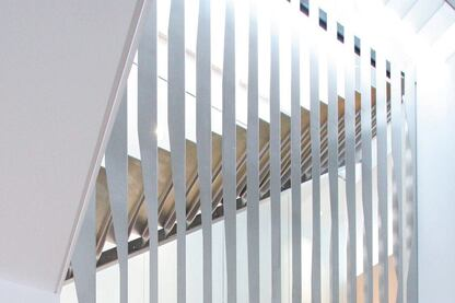 The design for the staircase is centered on folded stainless steel. Hung from a structural steel support on the top level of the townhouse, vertical folded pieces create a continuous screen that encloses the two above-grade flights of stairs. Tabs on the bent risers are fitted into slots on the vertical pieces, which created an easy setup for on-site construction and spot-welding.