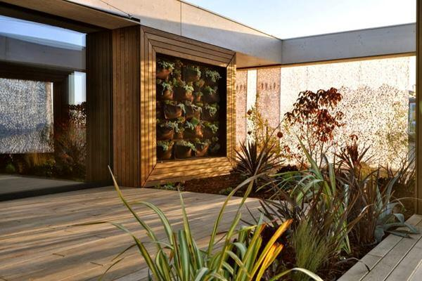 LISI, by Team Austria, features a living wall in both of its exterior courtyards, which are surrounded by fabric curtains that cast dappled shadows across the outdoor living spaces.
