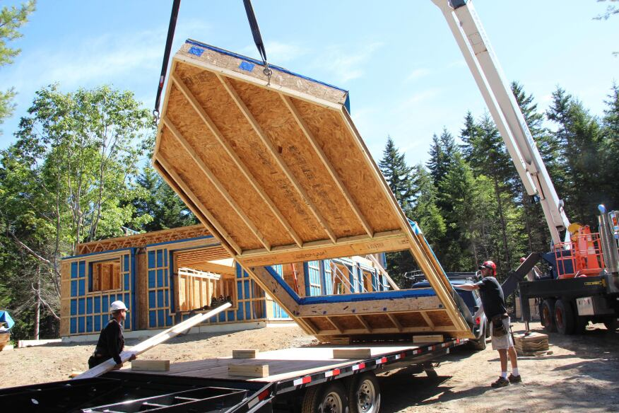 The crane lifts the largest gable end-panel off the trailer.