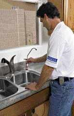 In a point-of-use reverse-osmosis water filtration system, a simple tap is installed at the sink.