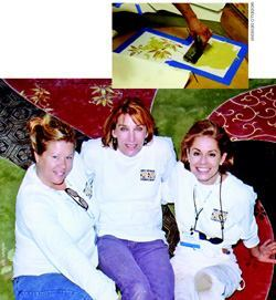 Right: Kari Caldwell, Melanie Royals, and Lee Gamble (left to right) relax on their slab completed at Artistry in Concrete 2005. Inset: A floral motif is embossed through a Modello with a thin layer of integrally tinted overlayment material. After the overlayment is dry and before the removal of the Modello, the designs are hand-colored with small brushes and dye stains.