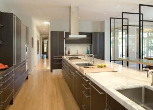 Gurney's visually seamless kitchen design still has to function, so he masked electrical outlets by having them pop up out of the island's surface. Roll-top doors hide countertop appliances, and custom-fitted butcher blocks slide to where they're most neeed.