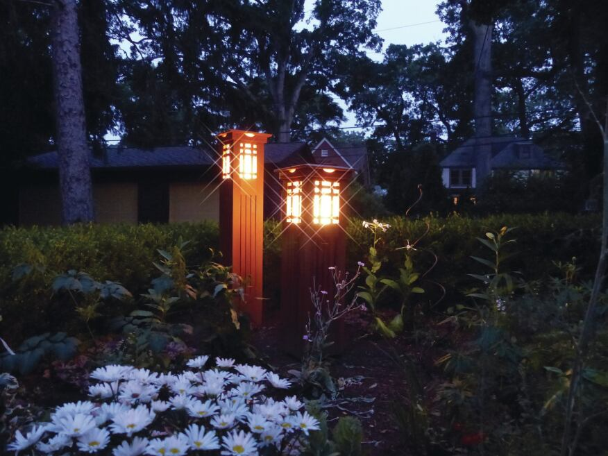 A pair of lighted columns in the garden are similar in design and construction to the corner column located on the deck, but vary slightly in size.