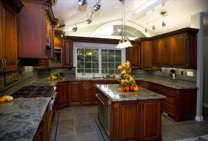 During the whole-house remodel, the Mackeys added 497 square feet to the kitchen so it could accommodate multiple cooks. A custom curved island uses every inch of space for appliances, a sink, storage, and plumbing access. They chose an undercounter refrigerator and oven and a custom-designed rangehood with pull-out spice racks. The space between counters in the kitchen is 42 inches wide to facilitate easy movement.