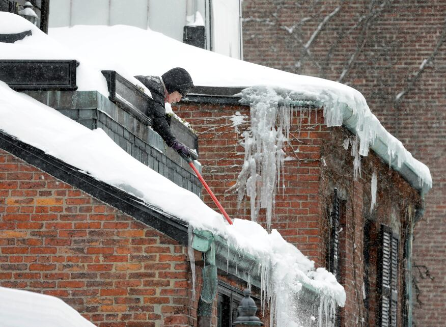 Susan Hartnett shovels snow from the roof of her Beacon Hill home in Boston.