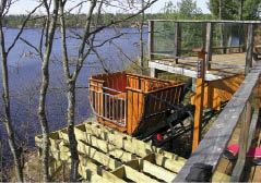The four-passenger car on this elevator overlooking Ontario's Muldrew Lake has been custom-finished with red cedar siding. To prevent it from blocking the view from the deck, a programmable controller sends it out of sight down the slope 15 minutes after it comes to a stop at the top station. Entering a use code on the post-mounted control panel (at right in photo) calls it back for another trip.