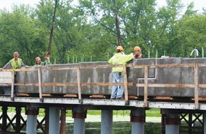 A crew sets a two-piece precast concrete pier cap into position on the State Route 25 Bridge, which bisects the Upper Mississippi National Wildlife and Fish Refuge.
