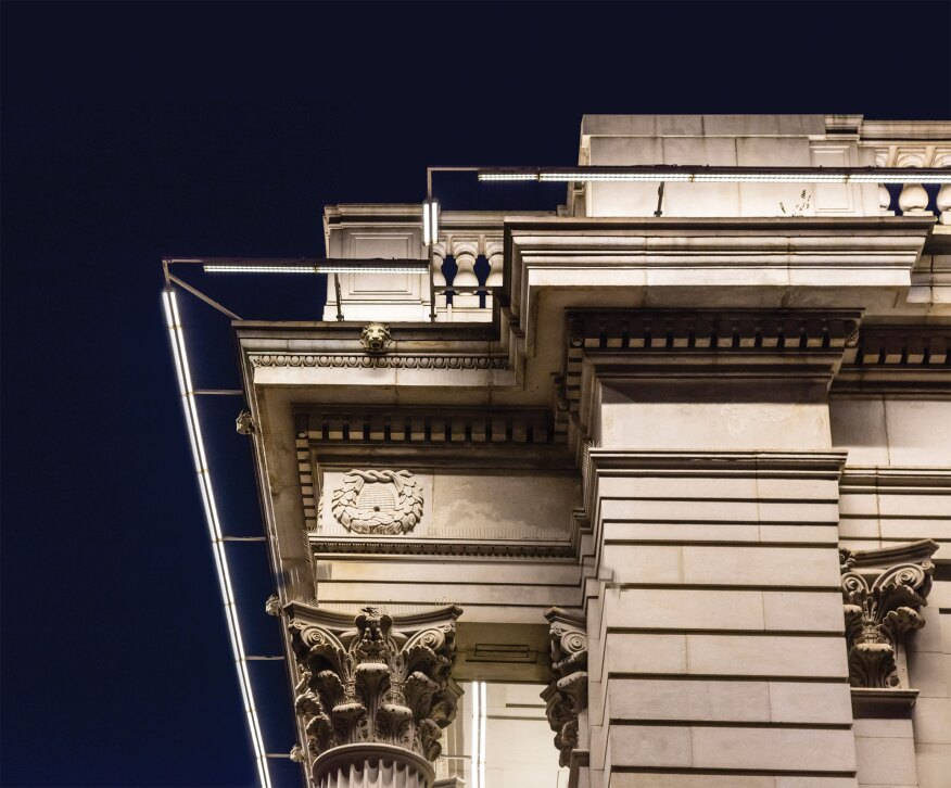 A custom mounting bracket system supports the custom-designed grazing luminaires, which feature two fixture heads, one with a 9-degree beam spread to illuminate the upper cornice and one with a 34-degree beam spread to wash the lower portion of the façade.