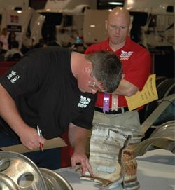 A judge watches a contestant during last year's SuperTech skills and knowledge competition. Such events are becoming more popular for recognizing young mechanics.