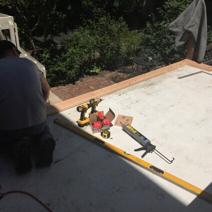 Working on top of the temporary roofing membrane, project manager Danny DoCouto began by installing the first of four layers of 2x10 SPF around the perimeter of the roof, to create a curb.