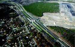 In addition to raising four lanes of the highway 25 feet to accommodate an underpass, Virginia  DOT's first design-build roadway project included two new  bridges, and 2.1 miles of new roads. There was just one major change order: when  APM Terminals rejected modifying an existing interchange in favor of  building the new diamond interchange pictured here. Photo: Skanska/Backus  Aerial Photography
