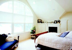 The new master bedroom's arched window wall frames a view of the lake.