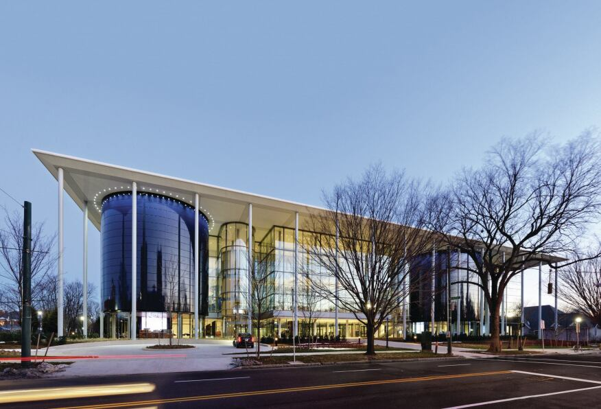 The main entrance to Edward P. Evans Hall is flanked by two curved volumes clad in blue glazing, which house stacked lecture halls on the upper levels.