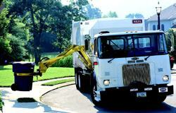 In automated refuse collection systems, an operator who never needs to exit the vehicle can run the truck.