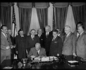 President Eisenhower signs H.R. 8127, authorizing the Interstate Highway System.